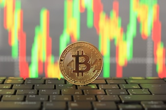 Bitcoin rate on the chart and gold coin, close-up