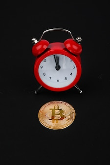 Bitcoin and red alarm clock on black space. cryptocurrency concept. gold color coin.