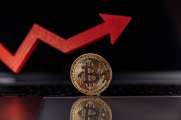 Bitcoin and red growth arrow close-up. ãâ¡ryptocurrency value concept.