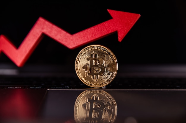 Bitcoin and red growth arrow on laptop cryptocurrency the rise in the value of bitcoin