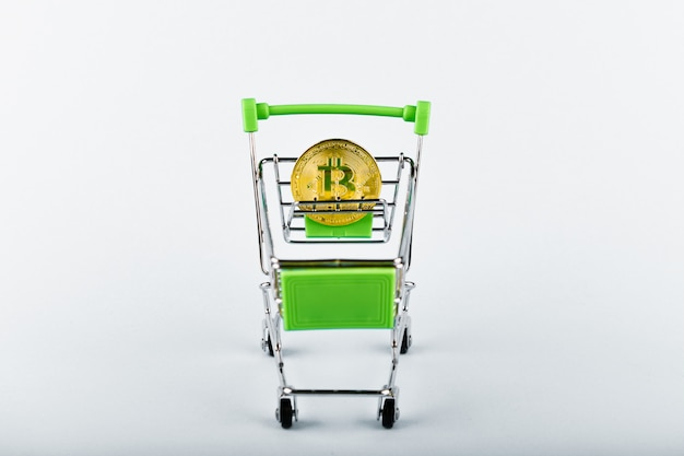 Bitcoin in a shopping cart on white