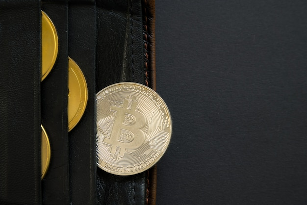 Bitcoin sticking out of a wallet o black surface.