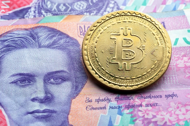 Bitcoin symbol at ukrainian paper currency background. cryptocurrency technologies concept.