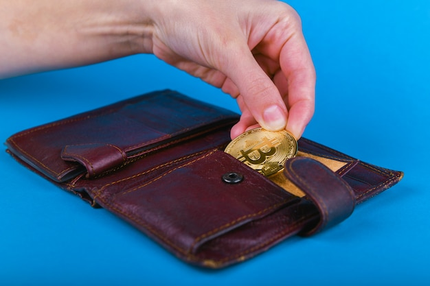 Bitcoin theft concept. hand steals bitcoin from a wallet.