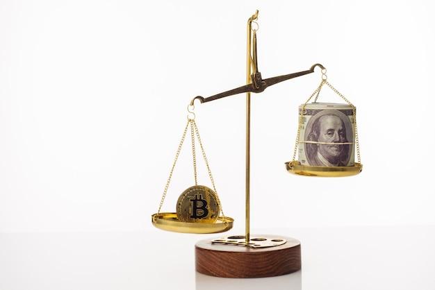 Тенденция увеличения стоимости биткойнов. монета перевешивает баланс. на другой чаше стопка стодолларовых купюр. белый фон - изображение
