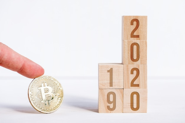 Bitcoin with numbers and 2019 on cubes on a white wooden background.