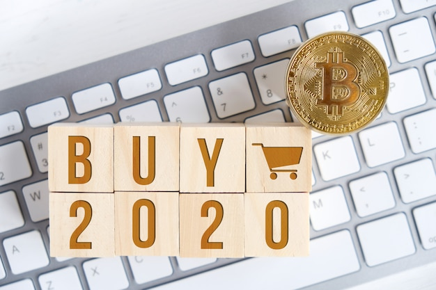 Bitcoin with numbers on wooden cubes on a white keyboard
