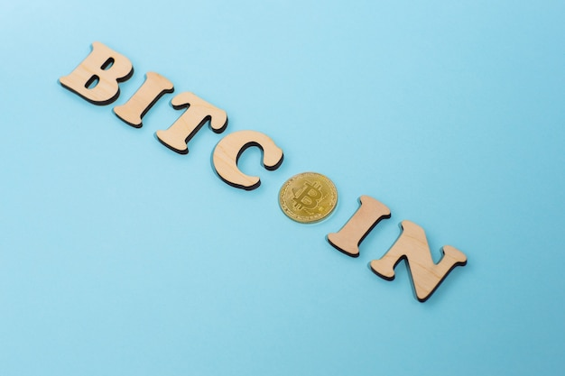 Bitcoin word composed of wooden letters and one bitcoin on blue surface