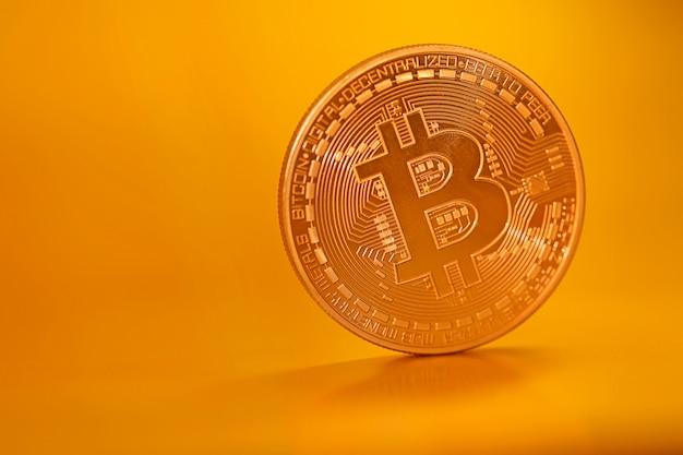 Bitcoin. виртуальные деньги. золотая биткойн-монета на золотом матовом фоне. криптовалюта