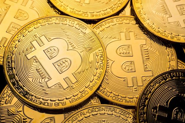 Закройте вверх золотых монеток с предпосылкой символа bitcoin.