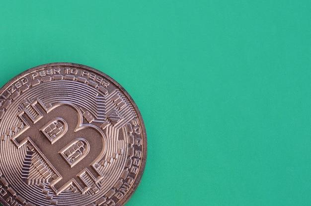 物理的なbitcoinの形のチョコレート製品は緑色のプラスチック製の背景にあります。