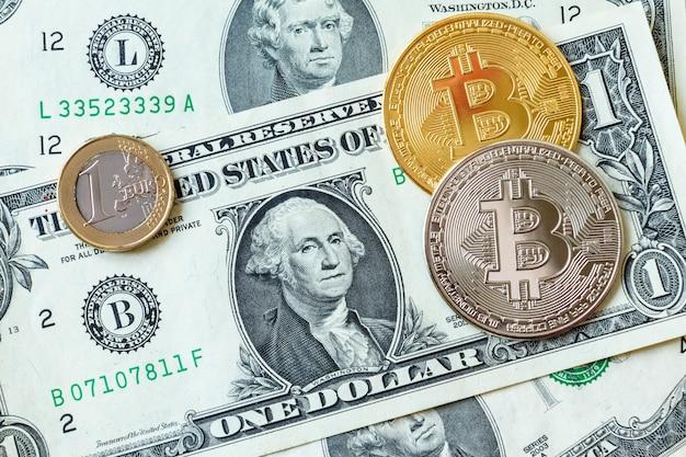Биткойны и монета евро на бумажных долларовых банкнотах