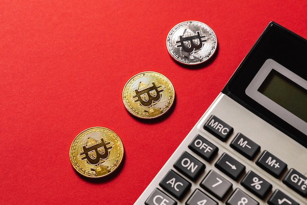 Bitcoins and calculator on a red table
