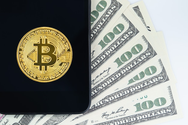 Bitcoins coin and  us banknotes of one hundred dollars with smartphone. close up of metal shiny bitcoin crypto currency coins and us dollar