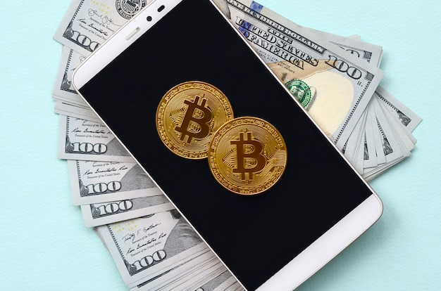 Bitcoins lies on a smartphone and hundred dollar bills on a light blue background