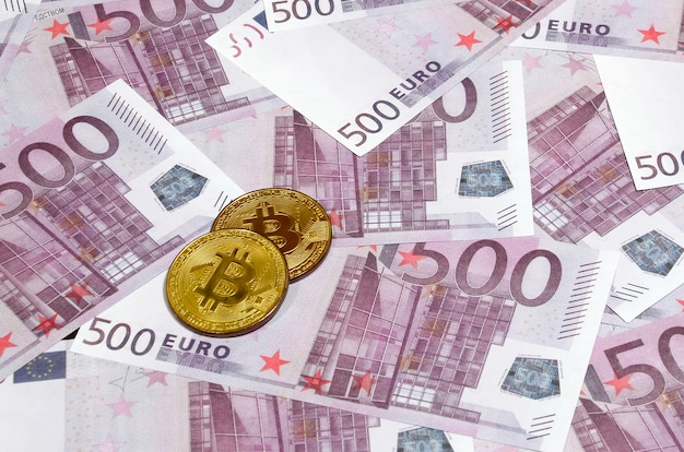 Bitcoins over pile of five hundred euro banknotes.