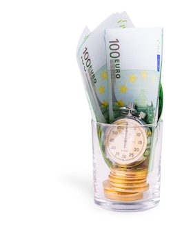 Bitcoins on a pile of one hundred euros and a bulb clock on empy glass