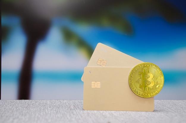 バックグラウンドでプラスチッククレジットカードとビットコイン。現金取引