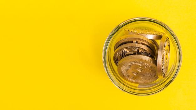 黄色の背景にガラスジャーのbitcoins