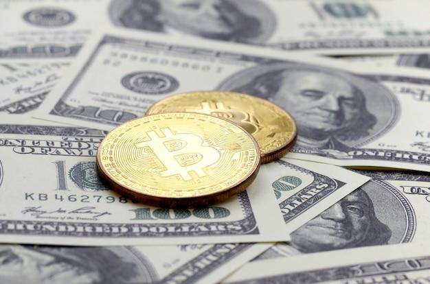 黄金のbitcoinsはたくさんのドル札の上にあります