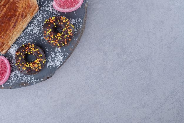 대리석 표면의 보드에 kyata 주위에 한입 크기의 도넛과 marmelade
