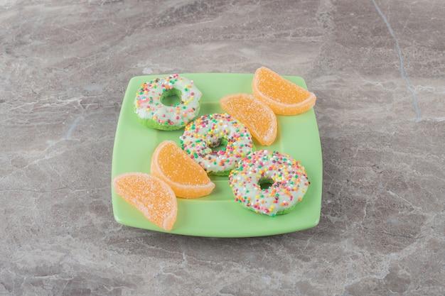 대리석 표면에 녹색 플래터에 배열된 한입 크기의 도넛과 마멜레이드
