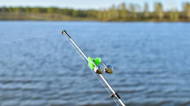Сигнал прикуса-звонка, на кончике удилища. насадка для удочки для ночной и дневной рыбалки. колокольчики предупредят вас об укусе. удочка во время рыбалки на озере, реке. рыболовная снасть