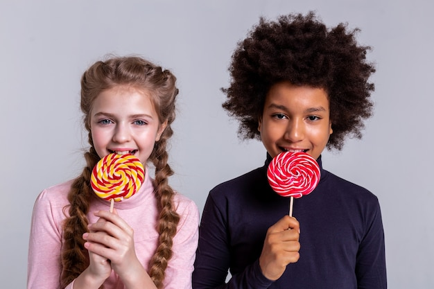 Biting hard candies. smiling dark-haired boy with black eyes eating candy while staying with blonde pretty girl