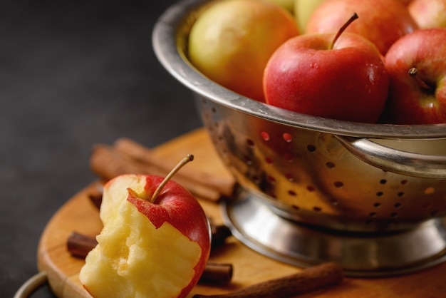 Bitten apple on cutting board with scattered cinnamon sticks on metallic bowl full of red ripe apples.