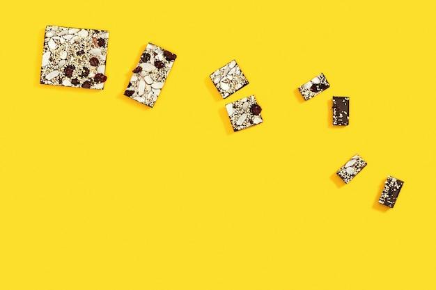 かまれたチョコレートの棒はいくつかの部分に分割され、ナッツとドライフルーツが入ったチョコレート