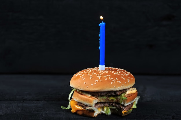 Bitten burger with a candle with fire