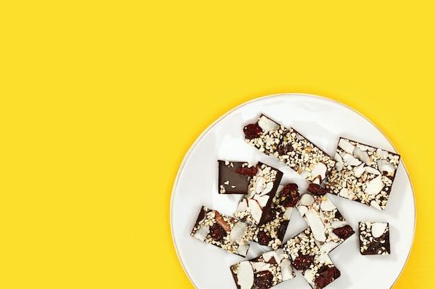 コピースペースと黄色の背景の上の白いプレートにナッツとドライクランベリーとかまれたチョコレートバー。お菓子。上面図、明るい色。