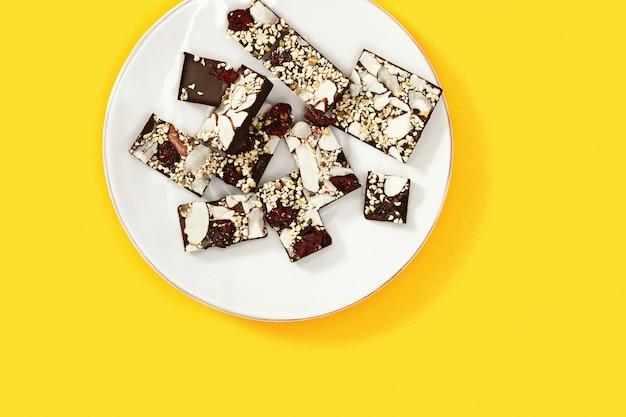 ナッツと黄色の背景に白い皿に乾燥クランベリーとかまれたチョコレートバー