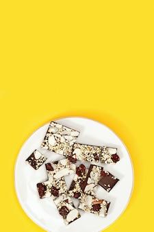 견과류와 노란색 달콤한 치료에 하얀 접시에 말린 된 크랜베리 물린 된 초콜릿 바.