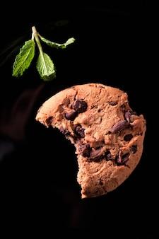Надкушенное шоколадное печенье и лист перечной мяты на черном фоне