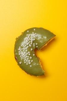 노란색 배경에 물린 크림 같은 말 도넛