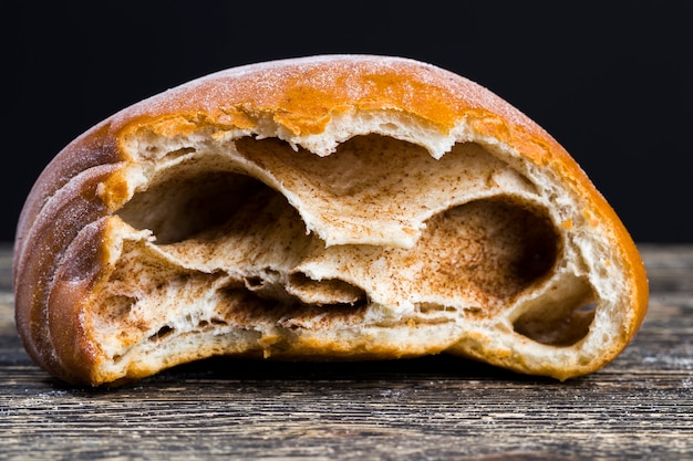 挽いたシナモンを詰めた、かまれた新鮮な小麦の柔らかいパン、クローズアップ