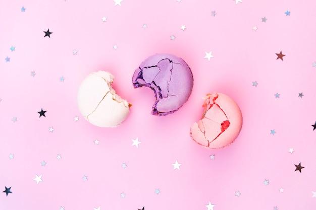 Надкушенное миндальное печенье на розовом фоне десерт из сладкого миндаля
