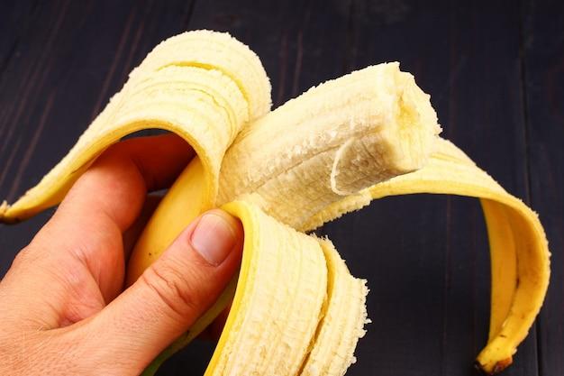 Откусил банан в руке крупным планом