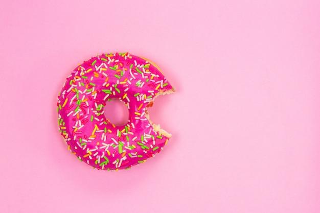 Укушенный розовый пончик на розовом фоне