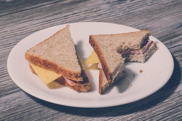 プレート灰色の木製テーブルの背景にかまれたサンドイッチ