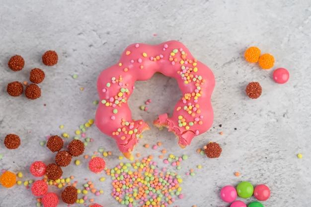 Укушенный клубничный пончик, украшенный глазурью и обсыпанный на полу