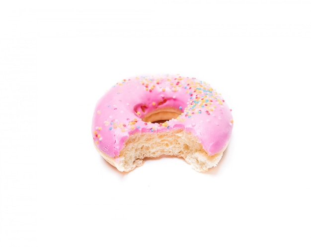 Bitten strawberry donut with colorful sprinkles isolated on white wall