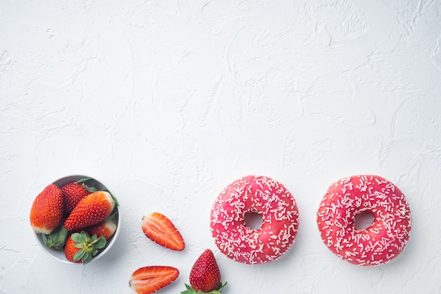 Bitten strawberry donuts, on white table, top view flat lay
