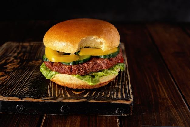 Bitten vegetarian burger on wooden board