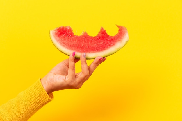 Bitten watermelon slice in hand over yellow background.  summertime concept.