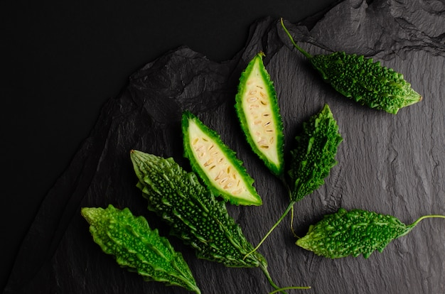 Bitter cucumber on black slate background. exotic cuisine . copy space, flat lay
