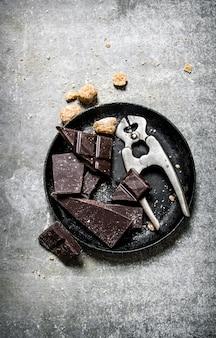 설탕을 곁들인 쓴 다크 초콜릿. 돌 배경.