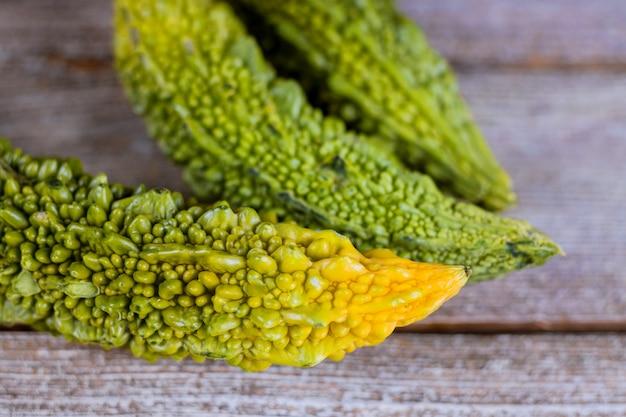 苦いメロン新鮮な有機グリーンハーブや野菜、苦いきゅうりや古い木製の背景に苦いきゅうり