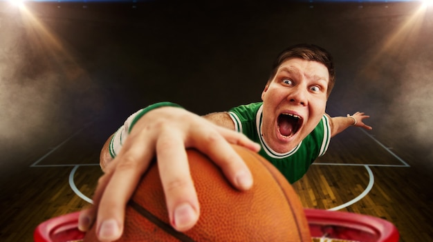 奇妙なバスケットボール選手がボールをバスケットに撃つ